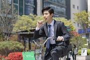 청년 신입사원의 하루 -  막대사탕을 먹으며 공유 자전거로 출근을 하는 활기찬 청년 신입사원