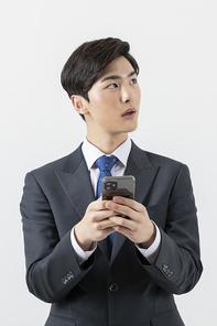 슬기로운 직장인 - 스마트폰을 들고 옆을 보고있는 직장인