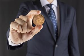 비트코인 - 양복입은 성인 남자 손에 들려있는 비트코인
