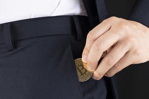 비트코인 - 양복바지에서 비트코인을 꺼내는 성인 남자의 손