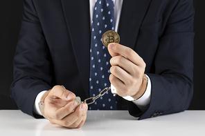 비트코인 - 수갑을 차고있는 양복입은 성인 남자 손에 있는 비트코인