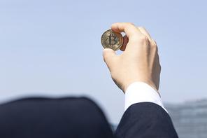 비트코인 - 맑은 하늘과 양복입은 성인 남자 손에 들려있는 비트코인