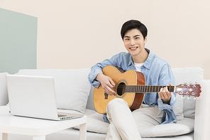 슬기로운 취준생 생활 - 쇼파에 앉아 노트북으로 강의를 들으며 기타를 연주하는 청년