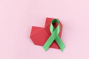 리본 - 분홍색 배경 위에 놓여있는하트 종이와 초록색 리본