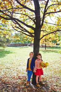 Happy little friends with yellow maple leaves