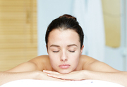 Young woman with closed eyes lying in spa salon and enjoying solitude
