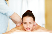 Young Caucasian woman lying in spa salon while masseur doing massage on her back