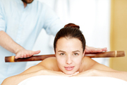 Calm brunette enjoying massage made up with wooden stick in day spa salon