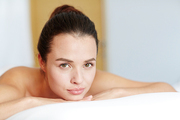 Relaxed young female with natural makeup looking at camera in spa salon
