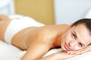 Young bare female looking at camera while relaxing in spa massage salon