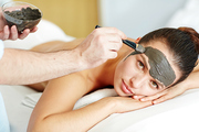 Beautician applying clay mask on female face in spa salon while she looking at camera