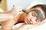 Woman relaxing in spa salon while cosmetician applying clay mask on her face