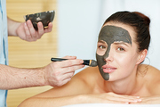 Beautician applying clay or carbon mask on face of young client in spa salon