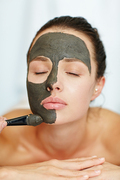 Young woman having rejuvenating clay mask on her face while visiting spa salon