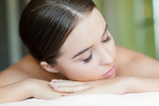 Relaxed girl with closed eyes lying in spa salon before bodycare procedure
