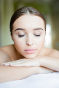 Relaxed woman with closed eyes having massage of her body in spa salon