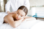 Relaxed young woman lying in spa salon and enjoying professional body massage