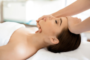 Hands of masseuse on forehead and chin of young client during procedure of spa facial massage
