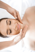 Happy girl smiling while enjoying facial massage in day spa salon