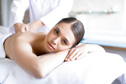 Relaxed woman looking at camera while enjoying spa massage in salon