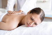 Young female feeling pain during body massage in salon