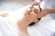 Young relaxed woman enjoying facial massage in professional spa salon