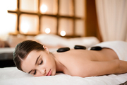 Serene girl with spa stones on her back relaxing in bodycare salon