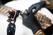 Tattoo machinery being used by master of tattooing
