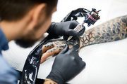 Modern tattooer painting on his client arm