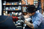 Tattooist drawing tattoo on skin of his client
