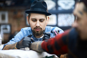 Concentrated master of tattooing during work