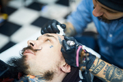 Master of tattoo art drawing on man face