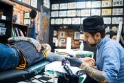 Young man visiting professional tattoo master