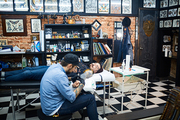 Creative young man drawing tattoo on arm of client