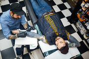 Stylish young man lying in tattoo-salon with master near by