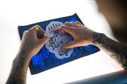 Creative tattooer making sketch of adornment