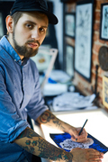 Bearded man in ball-cap making sketch of creative tattoo
