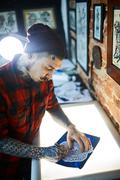 Creative man in tattoo workshop drawing adornment