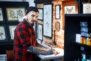 Young man making sample tattoo sketches in workshop