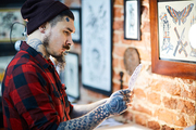 Hipster with tattooes looking at picture of drawn ornament