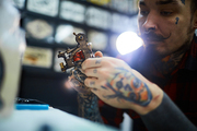 Tattoo-machine in hands of master