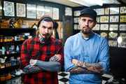 Stylish guys with crossed arms looking at camera in tattoo salon