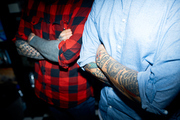 Two guys in shirts crossing their arms with tattooes on chest