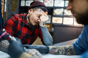 Client of tattoo salon feeling pain during process of tattooing
