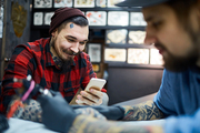 Happy hipster with smartphone visiting tattooist