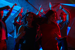 Ecstatic girls dancing by disco music with guys on background