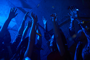 Friends dancing with raised hands in club