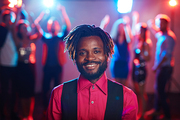 Waist-up portrait of attractive African-American with short dreadlocks smiling at camera cheerfully while hanging out in club