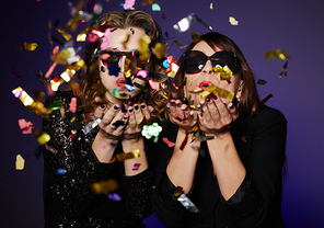 Attractive it girls wearing stylish clothes blowing colorful confetti while posing for photography in studio, waist-up portrait
