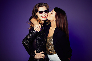 Group portrait of pretty young woman hugging her cheerful friend tenderly and kissing on cheek, studio shot